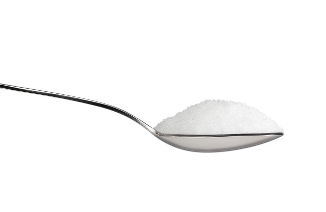 Salt or sugar on a teaspoon isolated on white background